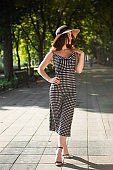 Beautiful young brunette woman dressed in a black dress and a hat with wide flaps takes a walk in a park during warm summer day enjoying sunlight.