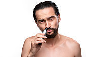 Handsome bearded man with mustache uses power trimmer to trim hair in the nose standing bare isolated over white background. Concept of morning routine and shaving.