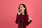 Happy young brunette woman singing and dancing using smartphone as a microphone and wearing wired headset.