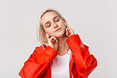 Pretty blond girl wearing red raincoat and white t-shirt dancing  listening to music with wireless earbuds. Concept of enjoying life.