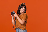 Excited brunette woman is happy to shoot with her camera.