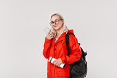 Blond girl in a red raincoat and glasses travelling with black backpack and white thermal mug in cold season. Rainy season.