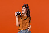 Happy brunette woman is happy to shoot with her camera.
