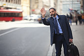 Senior businessman in the city using phone on the move