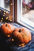 Closeup two orange pumpkins on gray knitted plaid near window in daylight surrounded with warm garland lights with golden bokeh.