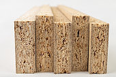 Particleboard with veneer is cut into small pieces. Materials for carpenters to build furniture. Light background.