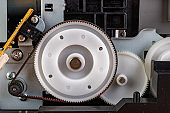 Small plastic ribbed gear. The mechanism in the home printer. Place - workshop.