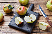 Red apples on a wooden table. Apples cut into slices. Copy space.