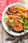 Grilled salmon steak, a portion of grilled salmon with fresh lettuce and potato wedges on a white ceramic plate