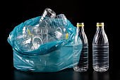 Empty plastic bottles in a garbage bag. Household waste collected in a blue bag. Dark background.
