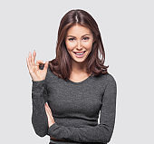 Portrait of beautiful smiling young woman showing okay sign