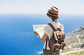 Tourist woman on vacations looking at map. Travel concept