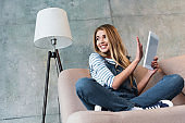 young girl smiling and turning away from monitor of digital tablet