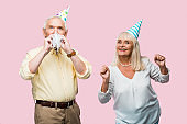 senior man covering face with party blower near cheerful wife in party cap gesturing isolated on pink