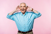 cheerful senior man touching ears and smiling while standing on pink