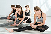 young people in sportswear practicing yoga in leg stretching pose
