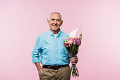 cheerful senior man standing with hand in pocket and holding bouquet on pink