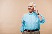 happy retired man talking on smartphone and standing isolated on beige