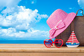Summer vacation concept with suitcase, sunglasses, hat and boat over sea beach background
