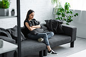 depressed young woman sitting on sofa at home and hugging pillow