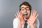 angry call center operator screaming on grey background