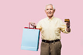 happy retired man holding credit card and shopping bags isolated on pink