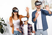 happy parents and cute kid wearing virtual reality headsets at home