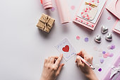 cropped view of woman writing on card near valentines decoration, gifts, hearts and wrapping paper on white background