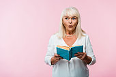 surprised senior woman with grey hair holding book isolated on pink