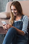 adult girl using smartphone and sitting near sofa