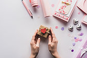 cropped view of woman holding valentines gift box with heart near pink decoration on white background