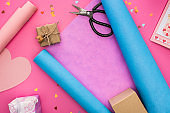 valentines confetti, scissors, greeting card, wrapping paper, gift box on pink background