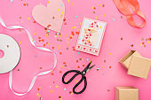 top view of valentines confetti, empty compact disk, scissors, gift boxes, greeting card on pink background