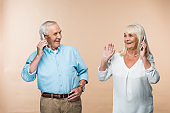 happy retired couple with grey hair using smartphones isolated on beige