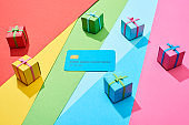 empty credit card and multicolored gift boxes on rainbow background