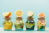 fresh detox drinks in jars with ingredients isolated on blue