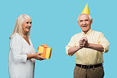retired woman giving yellow gift box to happy senior husband isolated on blue