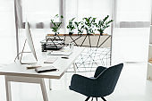 white table with computer, document tray, glass and notebook near office chair and flowerpot with plant