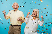 happy retired husband and wife gesturing near falling confetti on blue