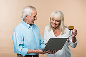 cheerful retired woman holding credit card near senior husband with laptop isolated on beige