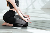 cropped view of barefoot woman practicing yoga in thunderbolt pose