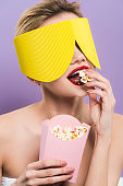 young woman holding bucket and eating tasty popcorn isolated on purple
