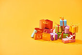 colorful wrapped festive gifts with shopping bags on bright orange background