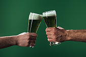 cropped view of men clinking  glasses of beer isolated on green, st patrick day concept