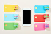 top view of multicolored empty credit cards, smartphone and gift boxes on white background