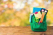 Back to school concept with bag backpack and school supplies on wooden table over autumn bokeh background