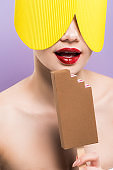 naked woman with red lips holding cardboard chocolate ice cream isolated on purple