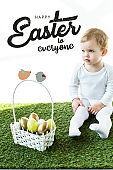 child sitting on green grass near basket with Easter eggs and happy Easter to everyone lettering above
