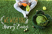 partial view of child holding toy carrot while sitting near Easter eggs and savoy cabbage on green grass with we wish you a happy Easter lettering