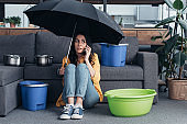 woman in jeans sitting in living room with umbrella and talking on smartphone